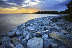 Sun set with rock dam sea coast bank protection perspective line Royalty Free Stock Image