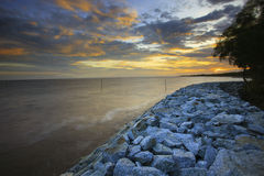 Sun set with rock dam sea coast bank protection perspective line Stock Photography