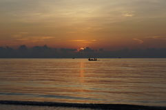 Sun set on the sea. The view of sun set on the sea. The local fishing boat past at the sky line Stock Photos