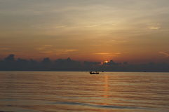 Sun set on the sea. The view of sun set on the sea. The local fishing boat past at the sky line Royalty Free Stock Images