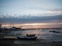 Sun set sky dramatic clouds sea front beach harbor marina boats Royalty Free Stock Images