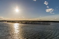 A sun set with star rays. setting over a pier and sea. royalty free stock images