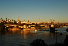 Sun sets on the beautiful Triana bridge on the Guadalquivir river, Sevilla, Spain. Discovering Andalusia, the beautiful region in the south of spain, for many royalty free stock photos