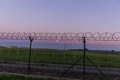 The sun sets behind a barbed wire fence. royalty free stock photo