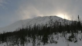 Sun sets behind big white hill covered with thick snow. Large sun disk sets behind massive white hill covered with thick snow against sparse winter forest stock video