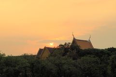 Sun sets behind Buddhist temple, Bangkok, Thailand Stock Images
