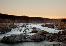 Sun sets behind Great Falls near Washington. Great Falls on the Potomac near Washington at sunset with the sun illuminating the trees stock image