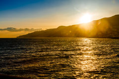 The sun sets behind the mountain Stock Photography