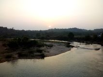 Sun sets behind the mountain. This is River Tungra gently flowing at Sringeri where Adi Sankaraacharya established the Saradha Mutt in Karnataka, India royalty free stock photo
