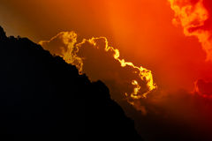 Sun sets behind mountain silhouette Royalty Free Stock Photography