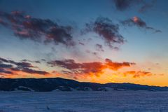 The sun sets behind the mountains and colors the clouds in winter, Altai, Russia stock image