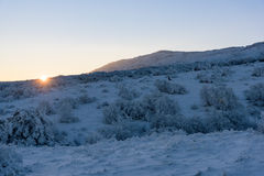Sun sets behind snowy mountain Royalty Free Stock Photo