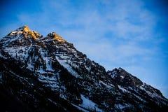 Sun sets on a mountain peak Stock Photography