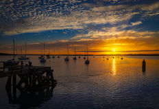 The Sun sets over Poole Harbor in Dorset. Hamworthy pier jetty Royalty Free Stock Photography