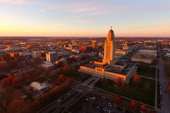 The sun sets over the State Capital Building in Lincoln Nebraska. Fall Color Orange Tree Leaves Nebraska State Capital Lincoln Downtown City Urban Skyline royalty free stock photo