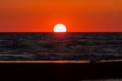 The sun sets. In the sea on a warm summer evening Stock Image