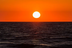 The sun sets. In the sea on a warm summer evening Stock Photography