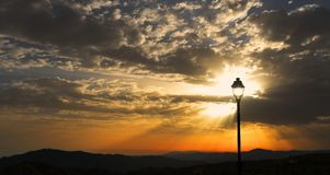 Sunbeams, viewed through a solitary lamp post, Sedella, Spain. Royalty Free Stock Photography