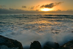 Sun setting above the horizon as viewed from Southern Breakwater Viewing Platform in Greymouth, New Zealand Stock Image