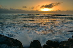 Sun setting above the horizon as viewed from Southern Breakwater Viewing Platform in Greymouth, New Zealand Stock Photo