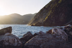 Sun setting against the Ligurian mountains by the ocean, creating golden vapors of waves hitting the rocks. Stock Photo