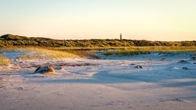 The sun is setting on the beach of Schiermonnikoog Friesland, Netherlands. The colortones are becoming warmer when the evening has arrived on the shore of the Stock Photo