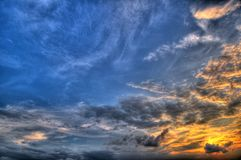 Sun setting behind the blue skies. Setting sun and dramatic clouds Stock Photo