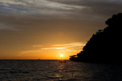 Sun setting behind a boat Royalty Free Stock Photos