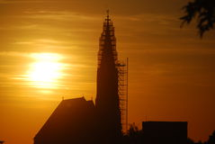 Sun setting behind church tower covered with scaffolding Stock Photo