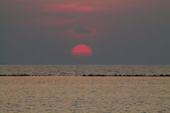 The sun setting behind the clouds to Karimunjawa Royalty Free Stock Photography
