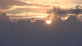 Sun setting behind clouds stock footage