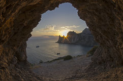 Sun setting behind the coastal cliffs. Crimea. Stock Photo