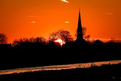 The sun is setting behind distant trees and a church in The Netherlands stock image