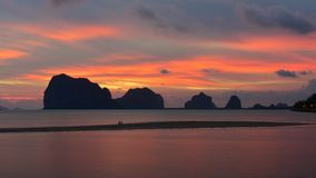 Sun setting behind the hilly islands and cliffs Royalty Free Stock Photography