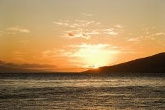 Sun setting behind island. Stock Photography