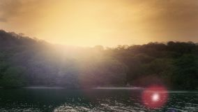 Sun setting behind an island beach. The sun as it sets behind a tropical beach. 4k UHD footage stock video footage