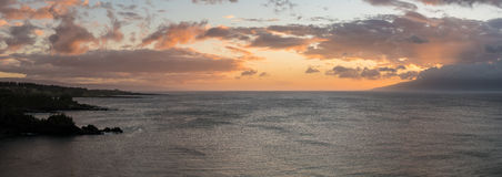 Sun setting behind the island of Molokai from Maui. Sunset with sunbeams from behind clouds as the sun drops below the mountains of Molokai. Taken from north Stock Image