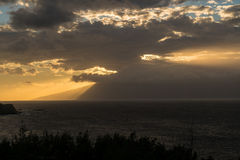 Sun setting behind the island of Molokai from Maui. Sunset with sunbeams from behind clouds as the sun drops below the mountains of Molokai. Taken from north Stock Images