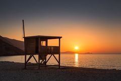 Sun setting behind lifeguard tower on Ostriconi beach in Corsica Stock Image