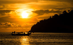 Sun setting behind longtail boat in Ko Lipe, Thailand. Sunset view from Pattaya beach in Ko Lipe, Thailand shows a longtail boat driving in front of the setting Royalty Free Stock Images