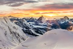 Sunset with mountains covered in snow. Sun setting behind the Matterhorn as seen form Monte Rosa, with mountains covered in snow Royalty Free Stock Photo