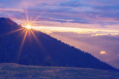 Sun is setting behind a mountain range. Epic sunset in the mountains - sun is setting behind a mountain range and shines with warm light all around. Vintage Royalty Free Stock Photo