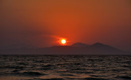 The sun setting behind the mountains. On the background Mediterranean orange colors dominate. clouds around the sun are shaped vortex Stock Photos