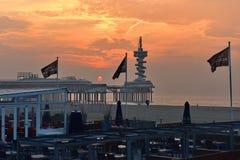 Sun setting behind the pier and restaurants along the sandy beach of Scheveningen Stock Photos