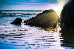 Sun setting behind rock formations in shallow water at the beach royalty free stock images