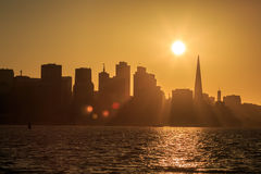 Sun setting behind San Francisco skyline casts golden shadows Royalty Free Stock Images