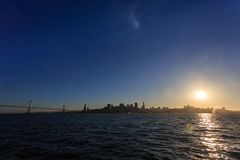 Sun Setting Behind San Francisco Skyline stock images