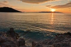 Sun is setting behind Skiathos island with some sea rocks in foreground at Kastani Mamma Mia beach, island of Skopelos. Greece Royalty Free Stock Photo