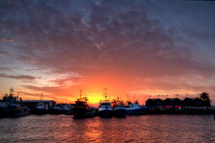 Sun setting between boats in Freo harbour Stock Photo