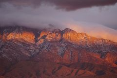 Sun setting on the cliffs of the Sandia mountains. Royalty Free Stock Photos